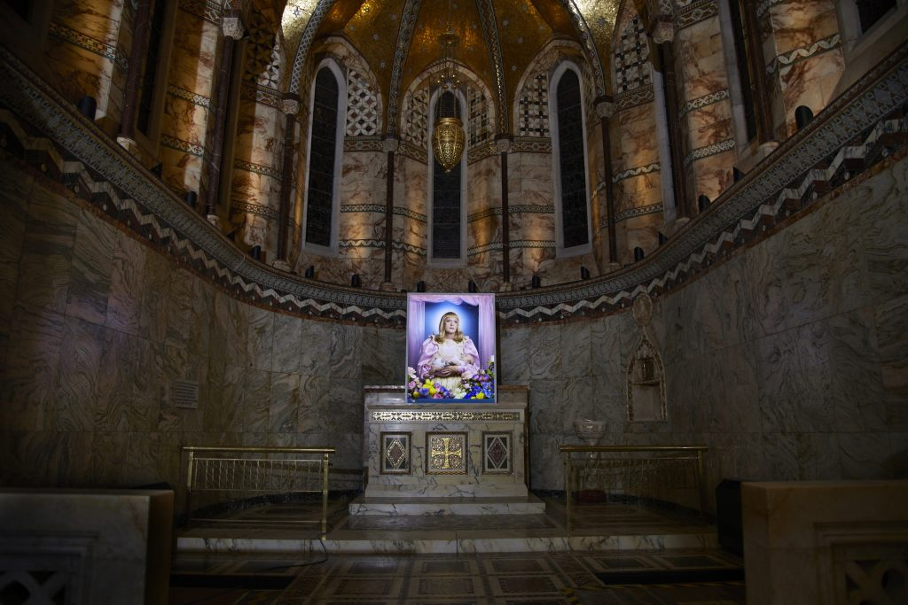"Created by renowned photographer Richard Ansett, this new portrait at the Fitzrovia Chapel focuses on Grayson Perry's alter ego, Claire.  'Claire is not a natural mother. This is a trans-immaculate conception and a perfect synergy with The Fitzrovia Chapel.' said Ansett of his new work 'Birth'. The 60×40″ photographic portrait is produced onto Kodak Duratran, then reverse mounted on acrylic, by our expert printing and<span class=""goldplus""> + more</span>"